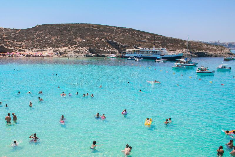 Swimmers in blue coastal waters of Malta royalty free stock photos