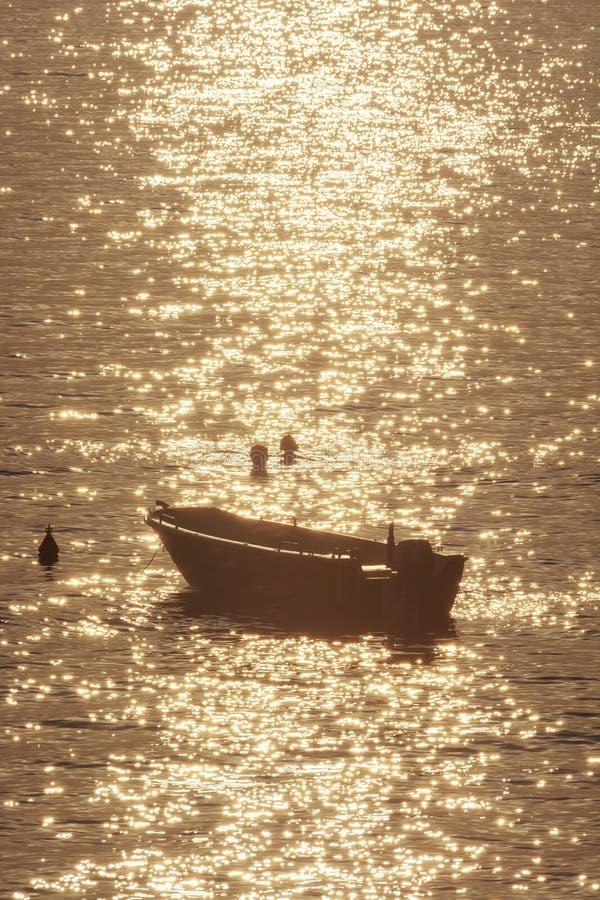 Swimmers and motor boat, sunrise in Mediterranean Sea, Solta, Croatia royalty free stock photo