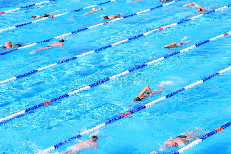 Outdoor swimming pool activities. Swimmers in several lanes practicing their swimming stroke. Outdoor activities royalty free stock photography