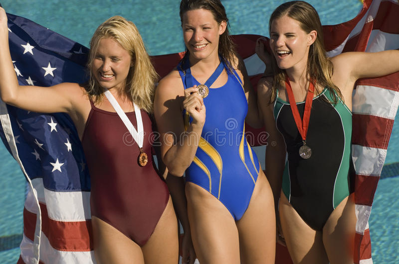 Swimmers Standing With Medals And Flag. Happy cheerful female swimmers standing with medals and American flag royalty free stock images