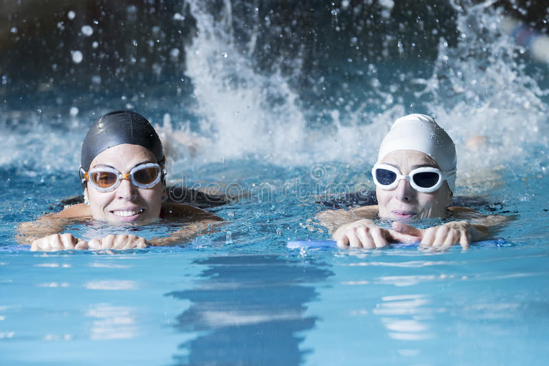 Swimmers swimming with a swim board. Couple of female swimmers swimming with a swim board doing leg exercises in an indoor swimming pool - focus on the right stock image