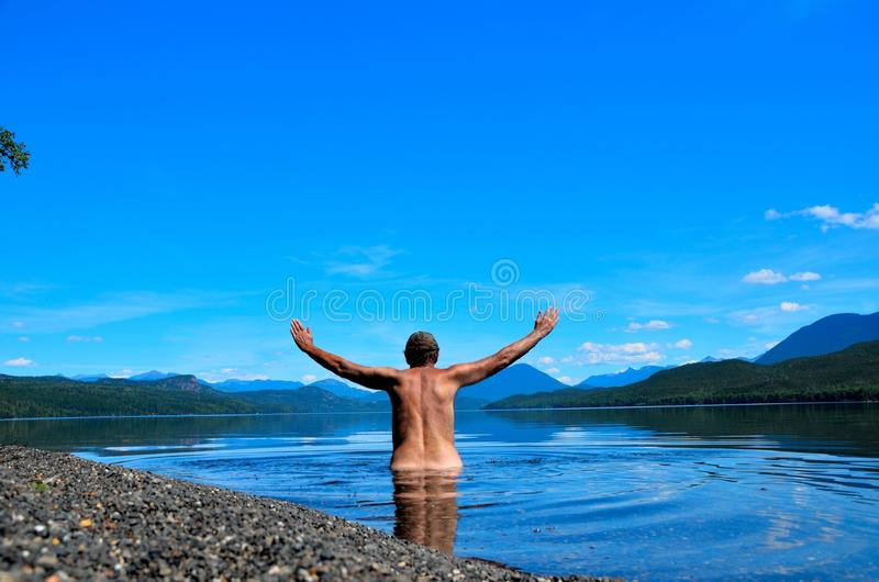 Swimming alone on a remote beach. Tanned man alone for 20 kilometers swimming on a remote beach on a crystal clear lake enjoying the solitude and peacefulness royalty free stock images