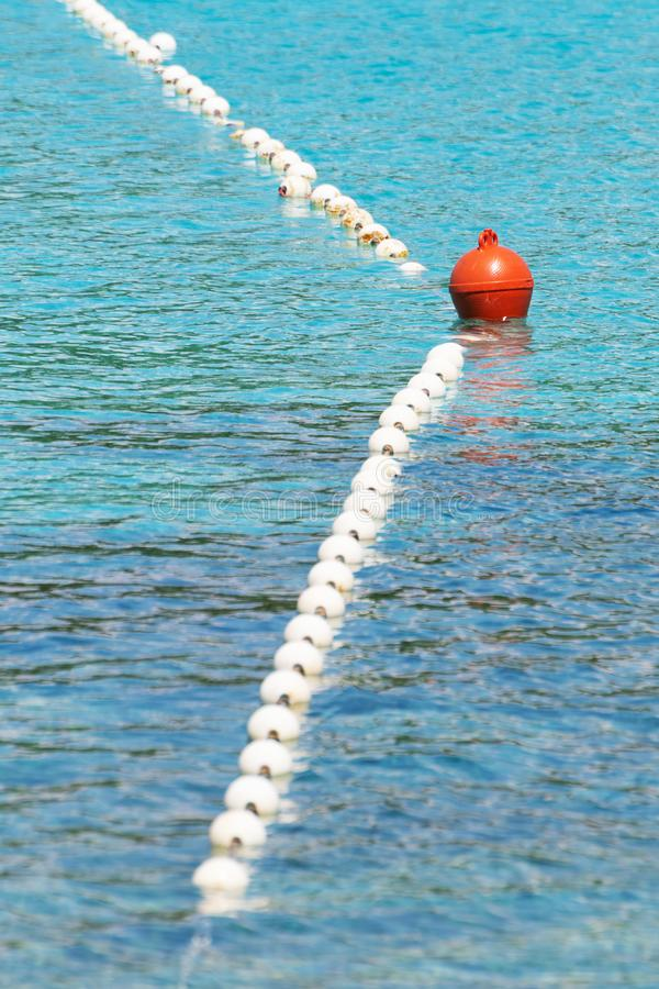 Swimming area barrier buoy rope floating on the turquoise colored sea. Vacation, travel, swimming, safety and protection concepts stock image