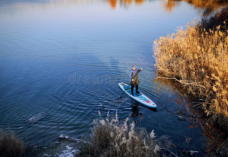 Swimming on the board on the water in the open air. Men swim on the SUP boards in the rays of the rising sun royalty free stock images