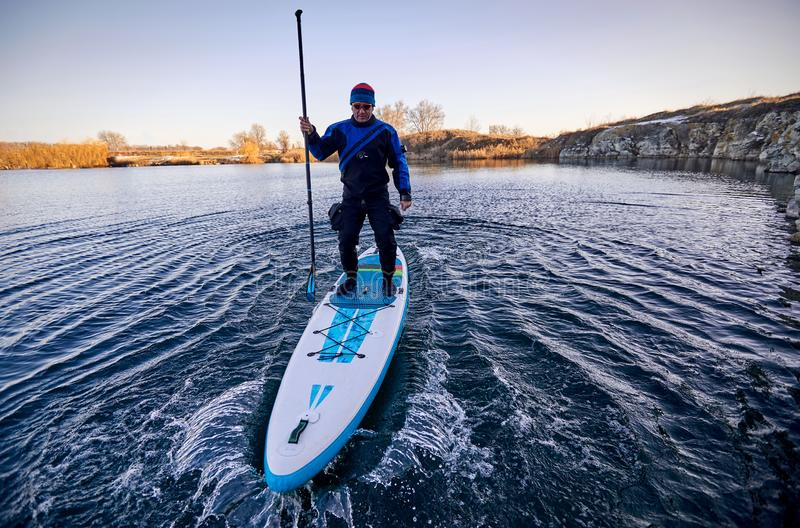 Swimming on the board on the water in the open air. Men swim on the SUP boards in the rays of the rising sun stock image