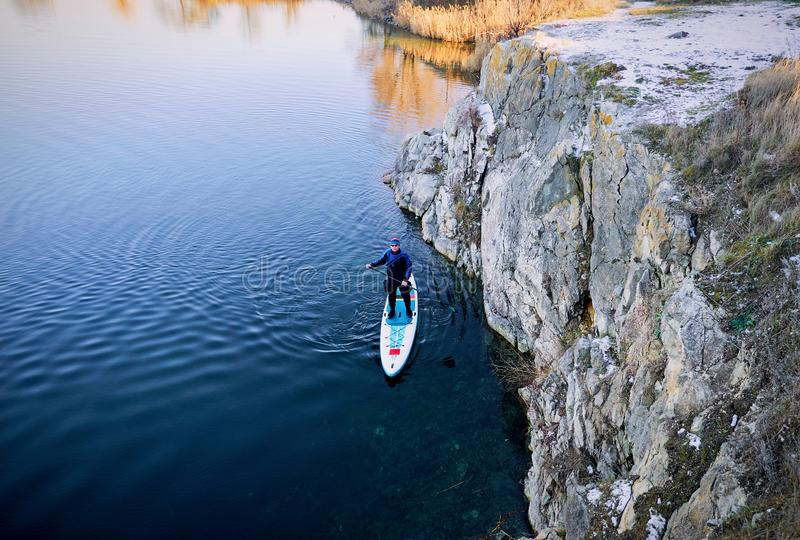Swimming on the board on the water in the open air. Men swim on the SUP boards in the rays of the rising sun stock photography