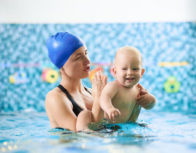 Mother with baby boy in swimming pool training stock photo