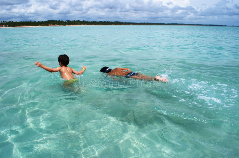 Swimming in crystalline clear waters sea in Brazil royalty free stock images
