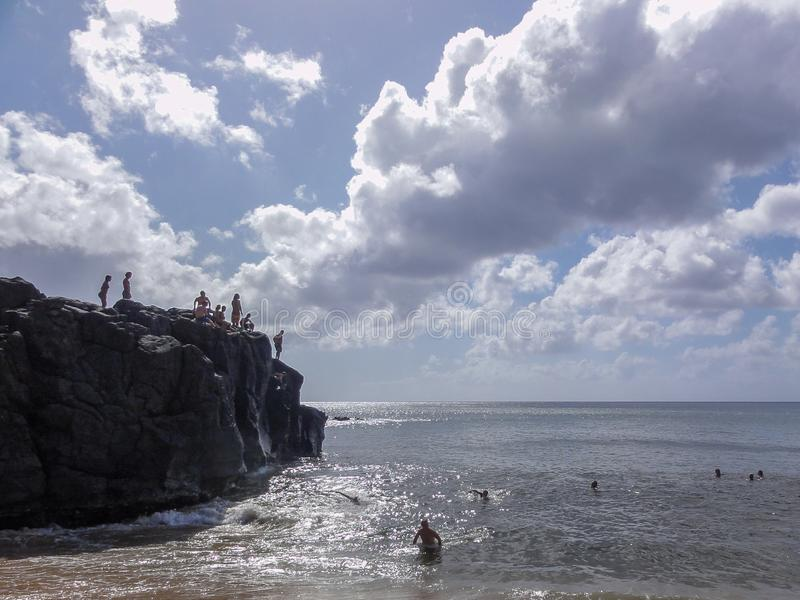 Swimming and diving at Waimea Bay. People standing on the cliff of Da Big Rock and swimmers at Waimea Bay located on the island of Oahu of Hawaii royalty free stock photo