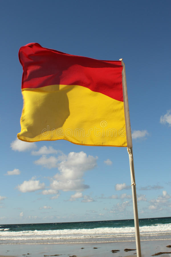 Swimming flag on the beach. Swimming yellow and red flag on the beach for safety stock image