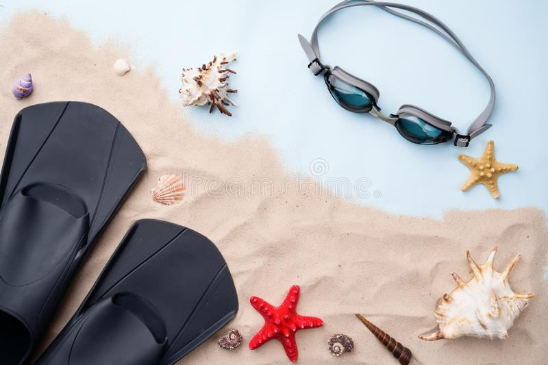 Swimming goggles and flippers on the sand with shells and starfishes. stock photography