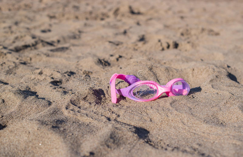 Swimming goggles on sand stock photo
