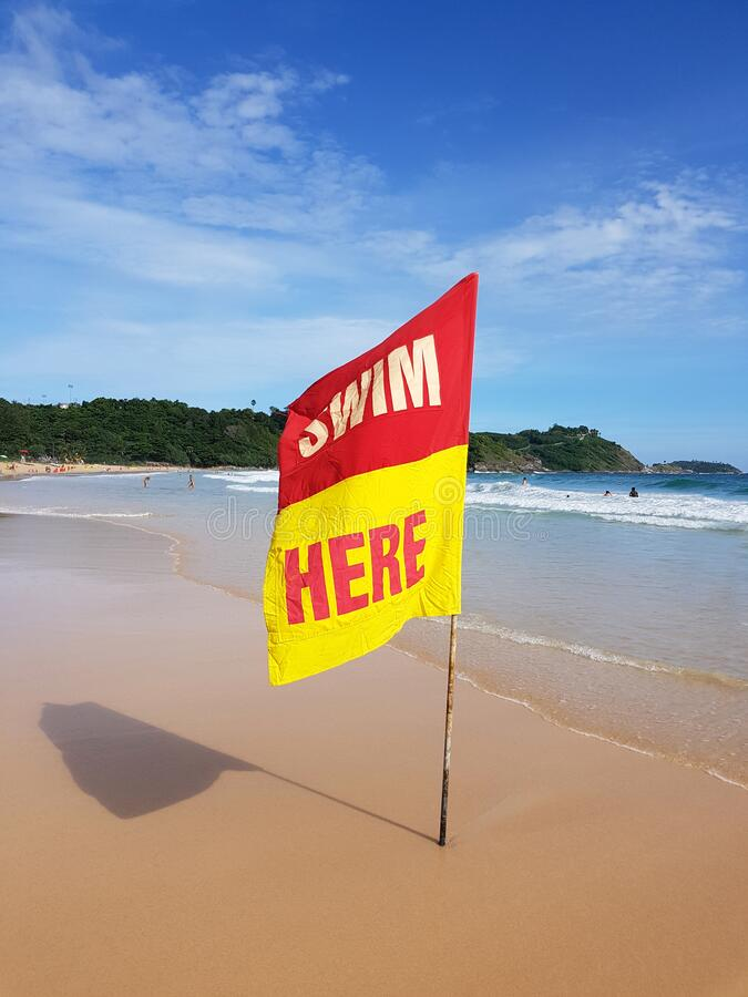 Swimming here sign flaf for security information on the beach stock image