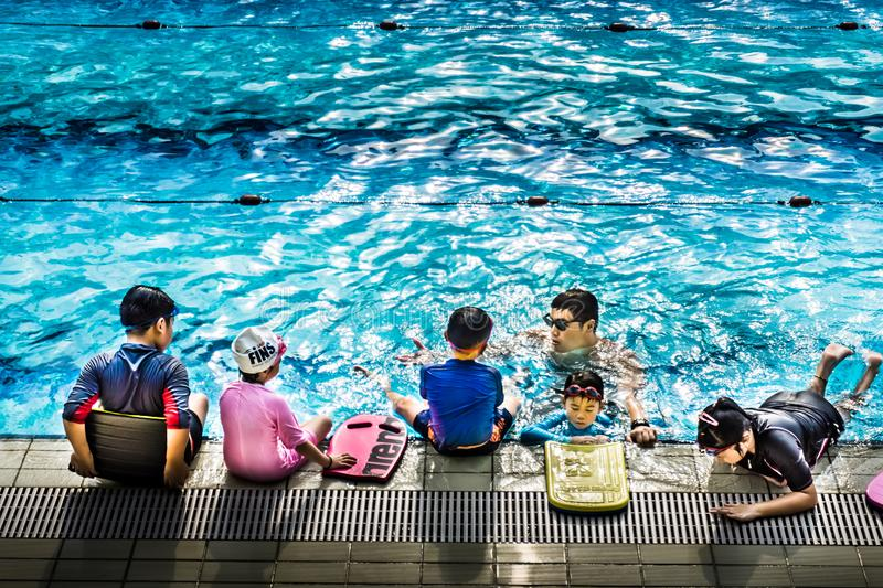 Swimming instructor coaching kids by the pool side royalty free stock photography