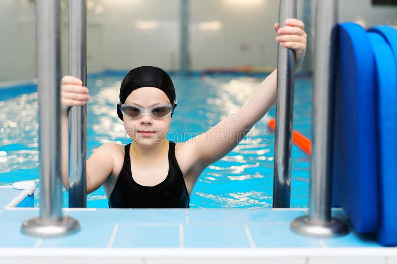 Swimming lessons for children in the pool - beautiful fair-skinned girl swims in the water stock images