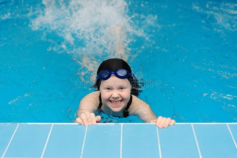 Swimming lessons for children in the pool - beautiful fair-skinned girl swims in the water royalty free stock photo