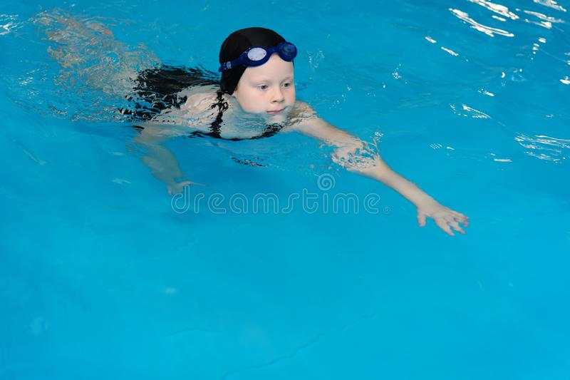 Swimming lessons for children in the pool - beautiful fair-skinned girl swims in the water stock photography
