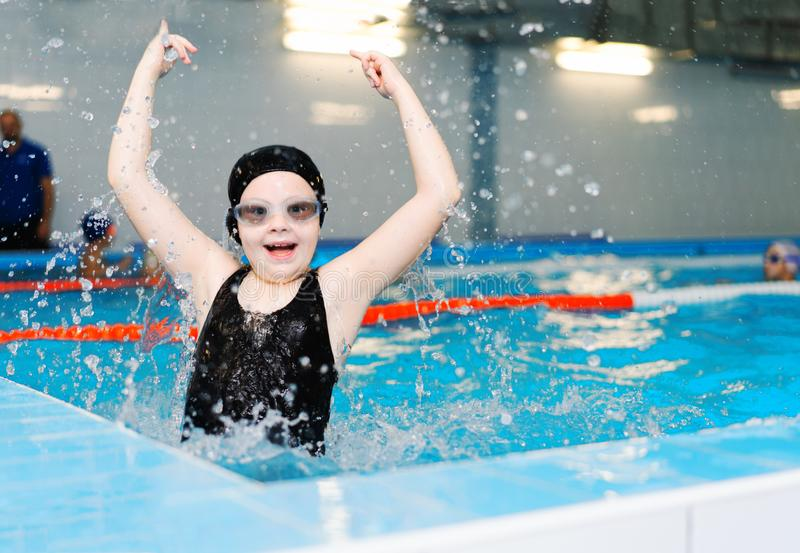 Swimming lessons for children in the pool - beautiful fair-skinned girl swims in the water royalty free stock photos