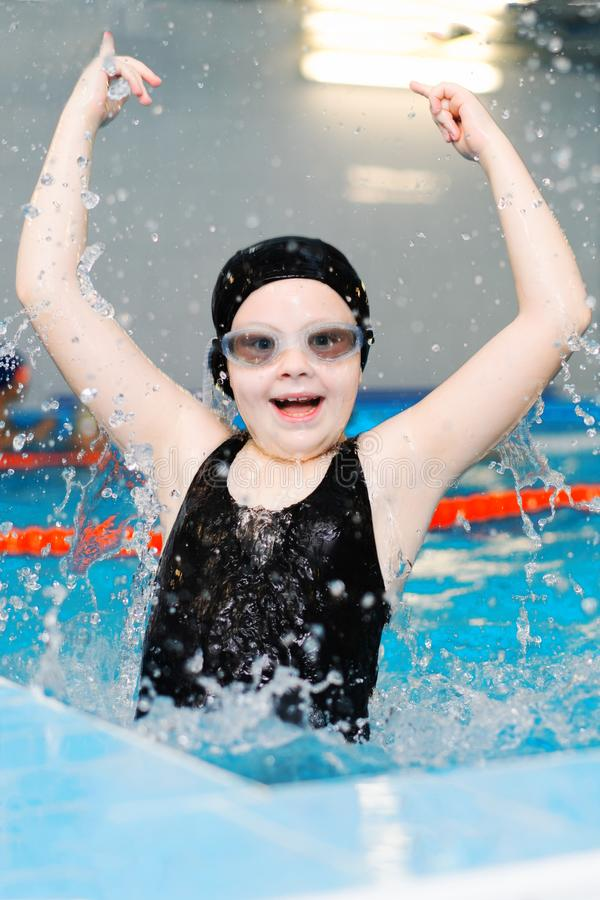 Swimming lessons for children in the pool - beautiful fair-skinned girl swims in the water stock photos