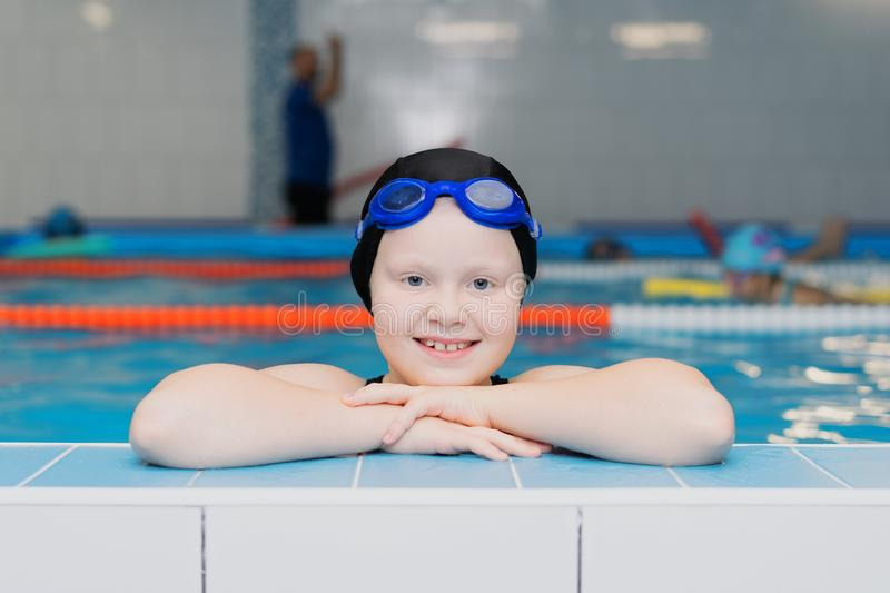 Swimming lessons for children in the pool - portrait of a beautiful white-skinned girl in a bathing suit and swim cap.  stock image