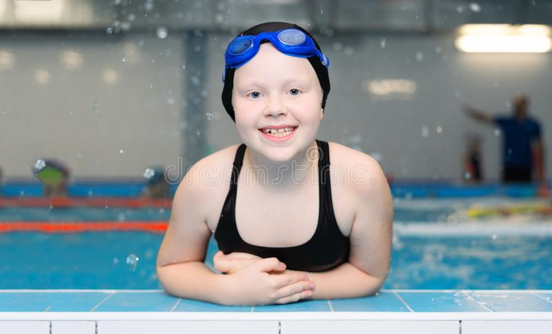 Swimming lessons for children in the pool - portrait of a beautiful white-skinned girl in a bathing suit and swim cap stock photos