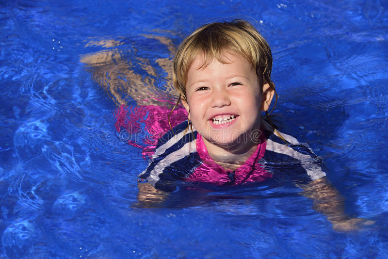 Swimming lessons: Cute baby girl n the pool royalty free stock image