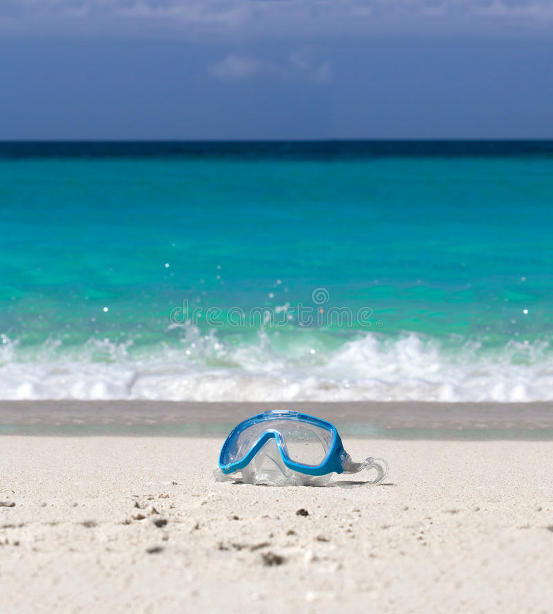 Swimming mask on white sand on tropical beach royalty free stock images
