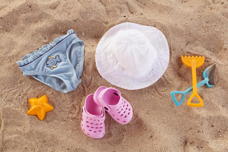 Swimming pool accessories for kids flat lay. Top view of children beach items on sand. Baby flip flops, hat and blue royalty free stock image