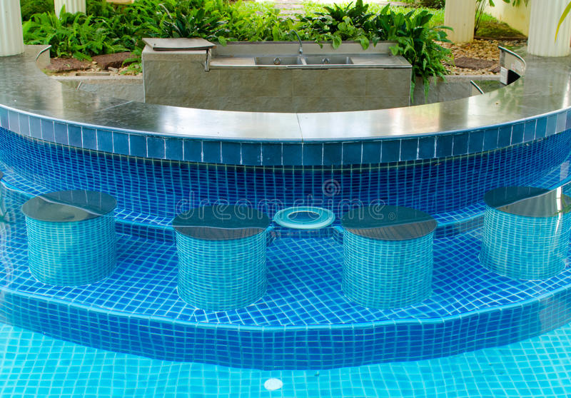 Swimming pool with bar. Blue water in hotel swimming pool with bar stock image