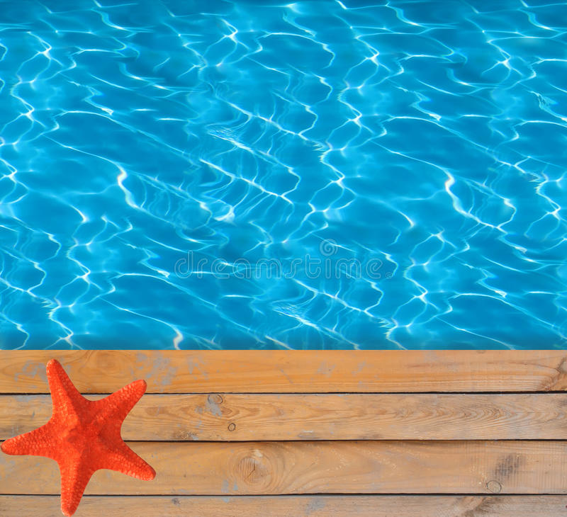 Swimming pool with blue clear water and wooden deck with star-fish stock images