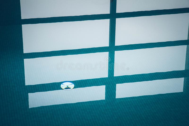 A Swimming pool. Blue still water in swimming pool with a reflection of windows visible stock images