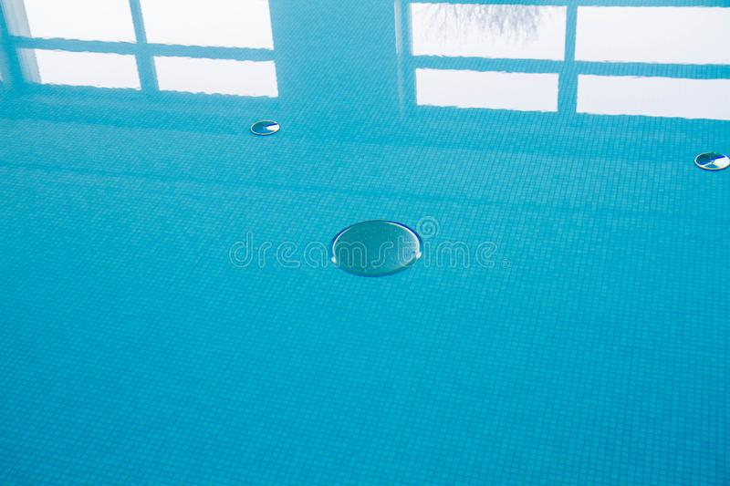 A Swimming pool. Blue still water in swimming pool with a reflection of windows visible royalty free stock photography