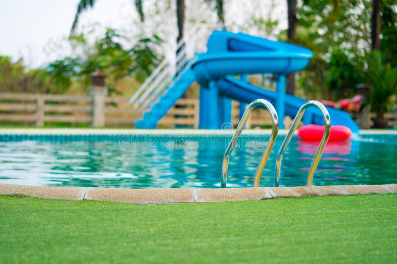 Swimming pool with blur of water slide background royalty free stock images
