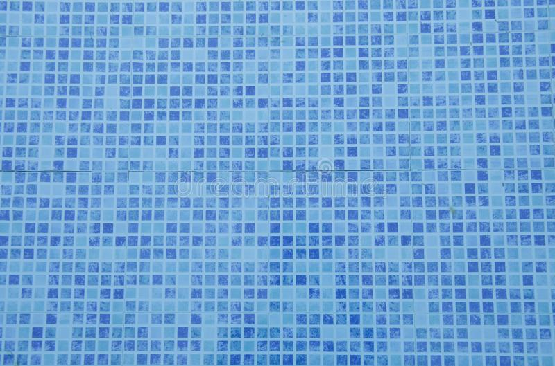 Swimming pool bottom. Close up view of blue mosaic tiles in the pool. Blue abstract ceramic tile. royalty free stock image