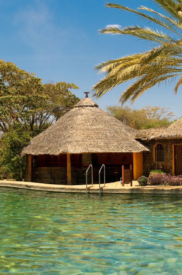 Swimming pool, bungalow and palm royalty free stock photography