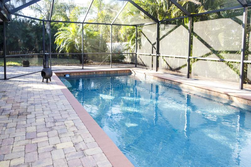 Swimming pool with pool cage. Home swimming pool with pool cage and paved patio for entertaining royalty free stock images