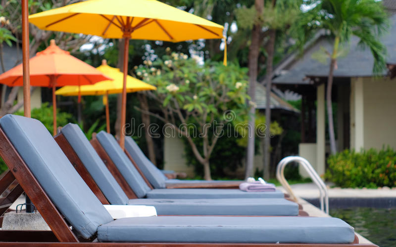 Swimming pool chair. Yellow Umbrella stock images