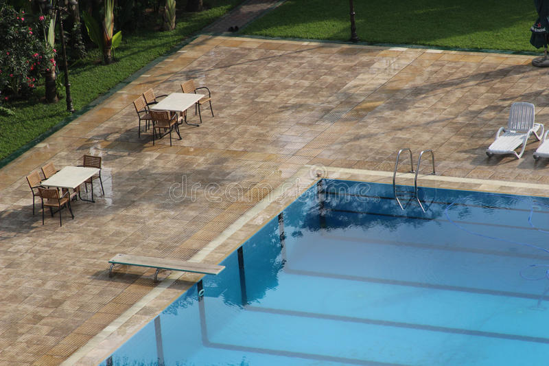 A swimming pool and chairs. A swimming pool with tables and chairs around royalty free stock photo