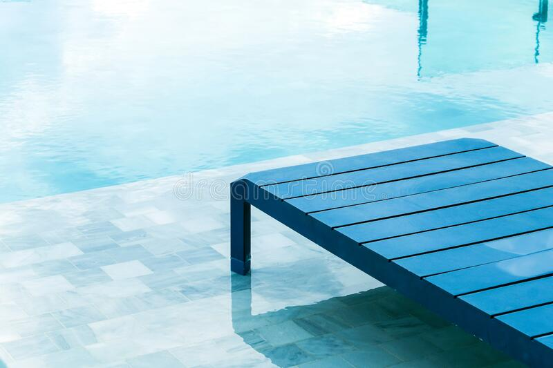 Swimming pool with chaise loungers royalty free stock photo