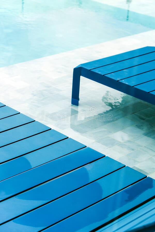 Swimming pool with chaise loungers royalty free stock images