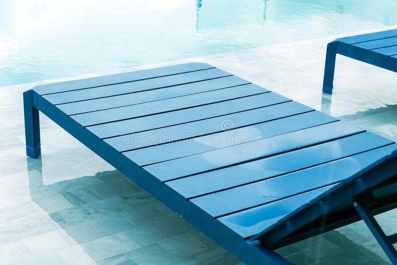 Swimming pool with chaise loungers royalty free stock photos