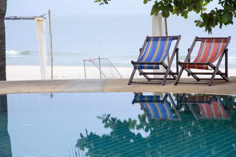 Swimming pool and deck chair under coconut palm trees at the resort with beautiful sea view stock image