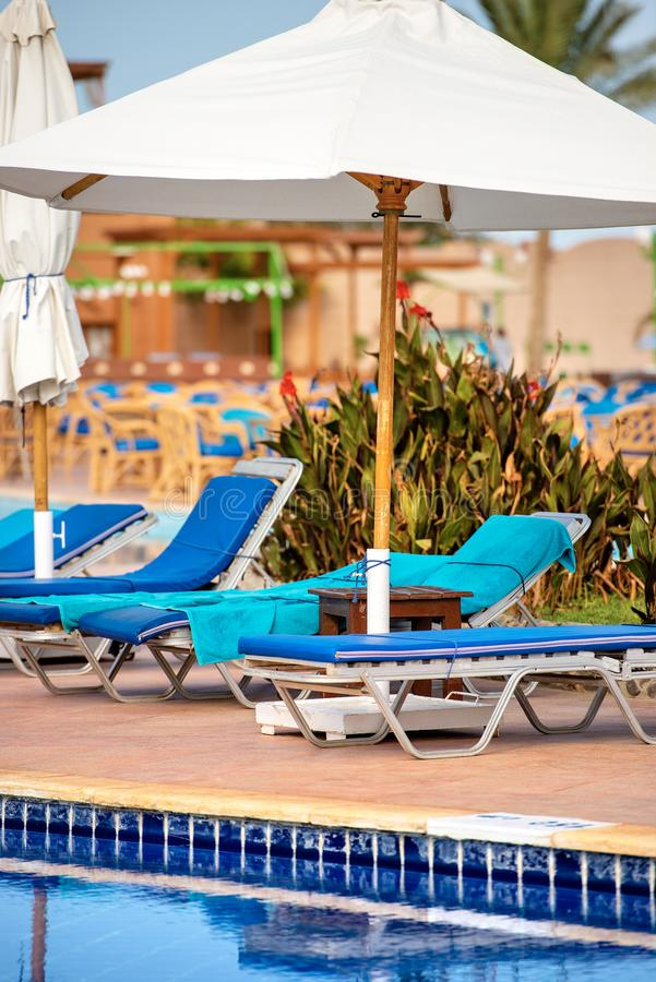 Swimming Pool with Deck Chairs and Beach Umbrellas royalty free stock photography