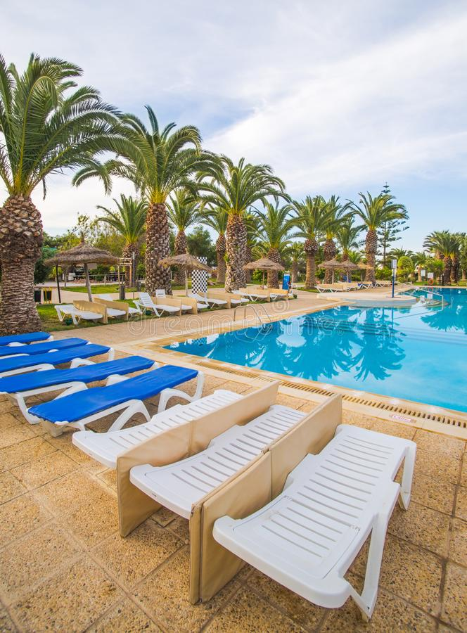 Swimming pool and deck chairs at luxury resort royalty free stock photography