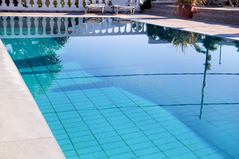 Swimming pool design modern architecture of luxury holiday villa. Relax near exotic swimming pool with handrail, deck chairs, sun. royalty free stock photography