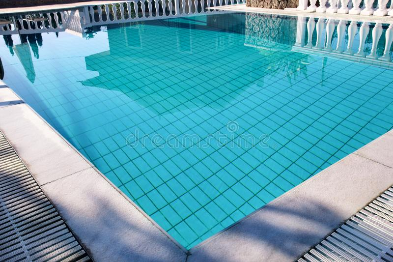 Swimming pool design modern architecture of luxury holiday villa. Relax near exotic swimming pool with handrail, deck chairs, sun. stock photo