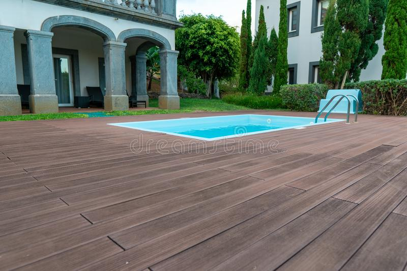 Swimming pool design with wood deck and modern villa royalty free stock image