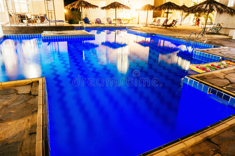 Swimming pool illuminated at night stock image
