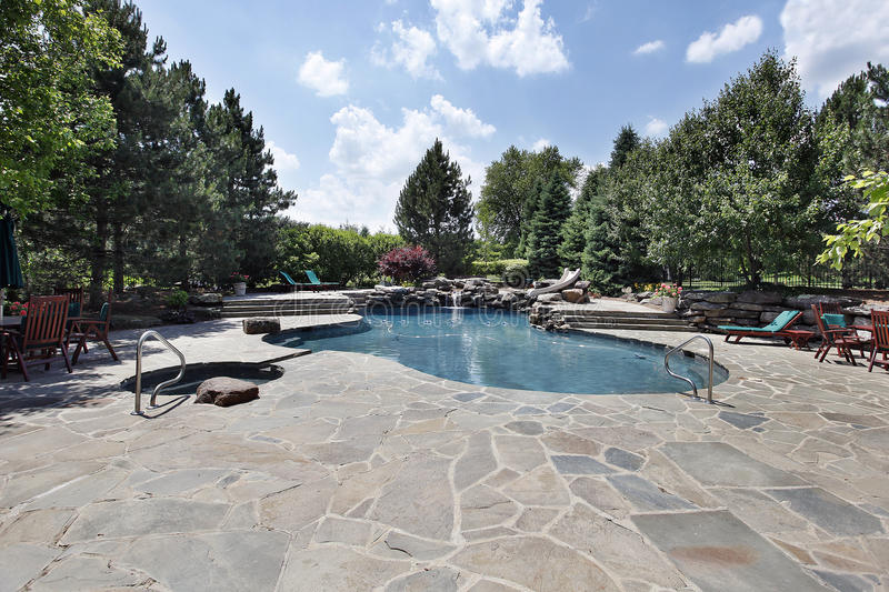Swimming pool with large stone patio stock images