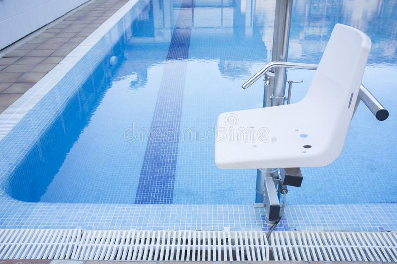 Swimming pool lift for disabled people access to the pool. Holidays resort background stock photos